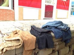 5 de Julio-Benidorm Ropa de hombre estaba doblada sobre una pequeña muralla, al lado de unos negocios.