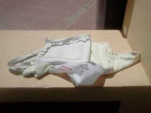 31 de Julio-Benidorm Un bolso bandolero y una blusa blanca encima de un banco en la calle.