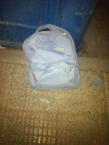 25 de Agosto-Benidorm Una mochila junto a un contenedor de papel.